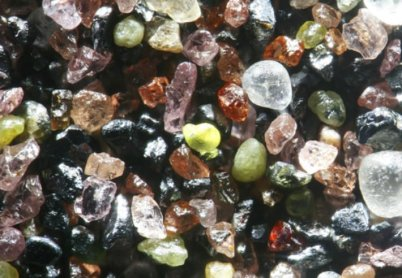 The glacially deposited sands around Lake Winnibigoshish, Minnesota, contain abundant sediments from the igneous and metamorphic minerals of the Lake Superior basin. A sample includes pink garnets, g